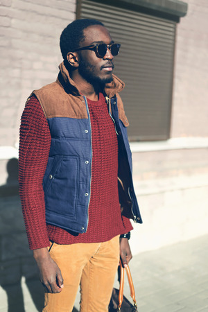 선글라스를 착용하는 패션 아프리카 남자, 니트 스웨터, 도시에서 조끼 재킷 저녁
