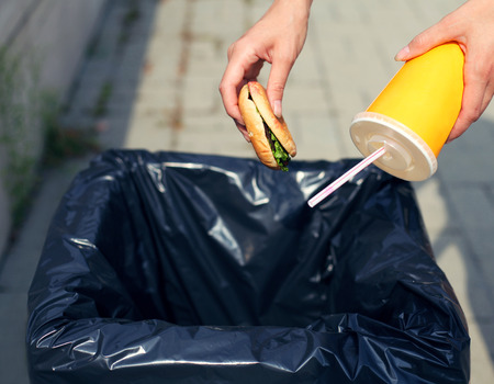 dumpster: Fast food and unhealthy eating concept - hand throwing a burger with a plastic cup in the trash on the street city