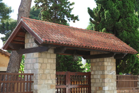 residence: Stone gate with the tiles on the roof, decorated facade Stock Photo