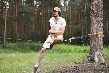 Sport, leisure, recreation and healthy active lifestyle concept - man slacklining walking and balancing on a rope, slackline outdoors in forest