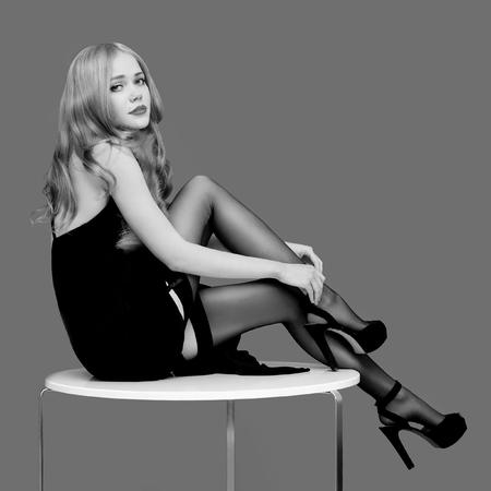 Schöne sexy Blondine in den Strümpfen und in den Fersen, die auf Tabelle, Schwarzweiss-Foto sitzen