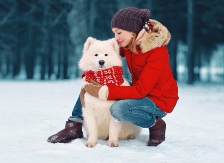 Happy caring young woman embracing white Samoyed dog in winter day