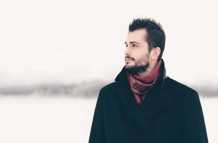 Winter portrait bearded elegant man looks aside on snowy background