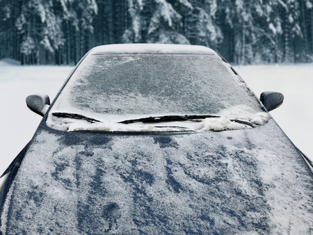 Frozen winter car covered snow, view front window windshield and hood on snowy background Standard-Bild