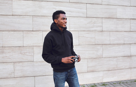 Happy smiling young african man with vintage film camera in black hoodie walking on city street over gray brick wall background