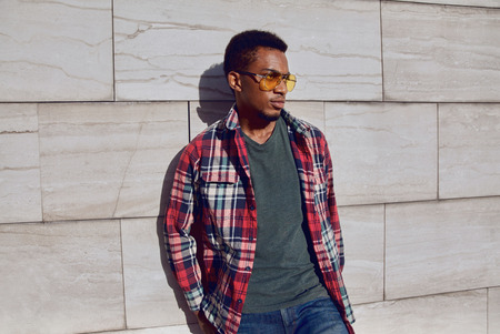 Stylish african man wearing red plaid shirt, looking away, guy posing on city street, gray brick wall background