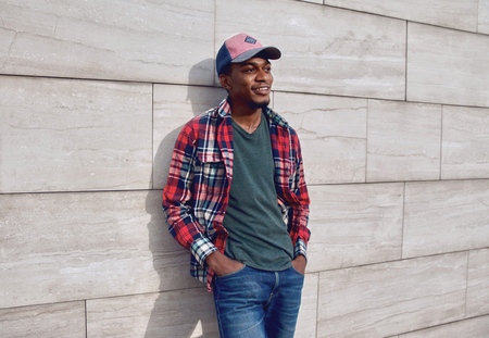 Stylish smiling african man wearing red plaid shirt, baseball cap on city street, gray brick wall background