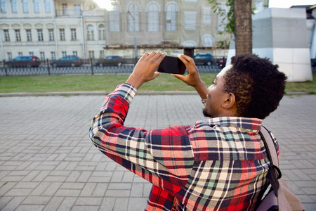 Closeup african man taking picture by phone on city street