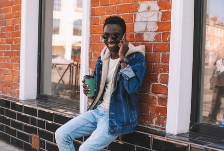 Happy smiling african man calling on smartphone sitting with coffee cup on city street, brick wall background
