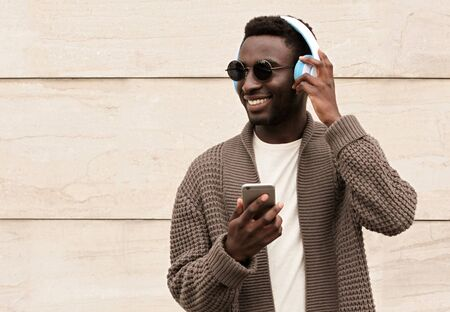 Portrait stylish smiling african man with phone in wireless headphones listening to music wearing brown knitted cardigan and sunglasses on city street over brick wall background Фото со стока