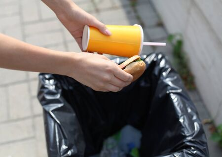 Fast food and unhealthy eating concept - hand throwing a burger with a plastic cup in garbage can on the city street Standard-Bild