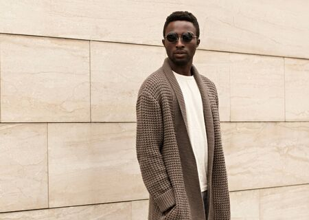 Stylish african man model wearing brown knitted cardigan, sunglasses on city street over brick wall background Фото со стока