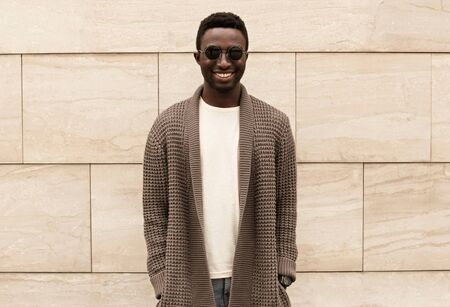 Stylish smiling african man wearing brown knitted cardigan and sunglasses on city street over brick wall background Фото со стока