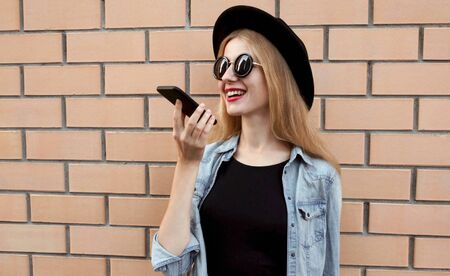 Portrait of smiling young woman with phone using voice command recorder, assistant or takes calling on city street over brick wall background Foto de archivo