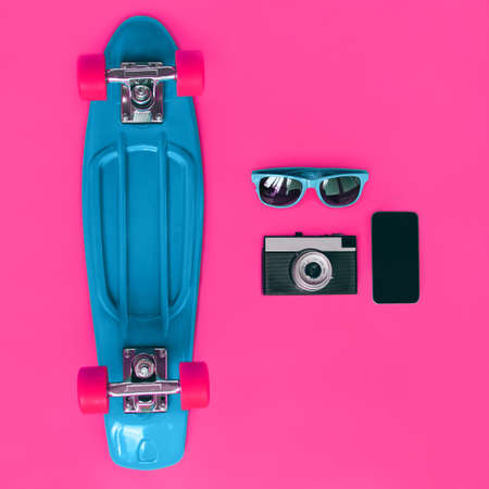 Colorful stylish set, blue skateboard, sunglasses, vintage film camera and smartphone screen on a pink background, top view, flat lay