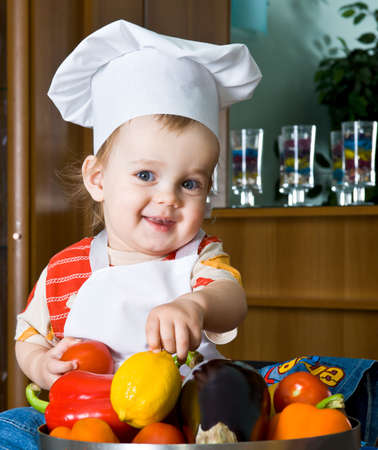 funny fruit: Baby in the cook costume in the white hat with vegetables