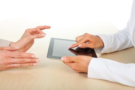 Office - Two businesswomen working with digital tablet