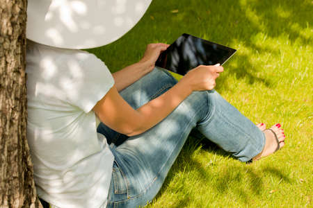 Young woman in hat sitting on the grass with digital tablet. Stock Photo