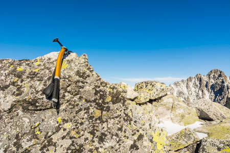 ice axe: Ice axe hung on a rock in the mountains