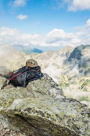 Helmet, backpack and trekking poles photo
