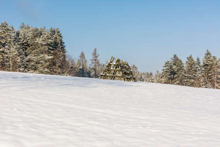 haymaking: Landfill hay field (stand) on a meadow covered with snow waiting for haymaking Stock Photo