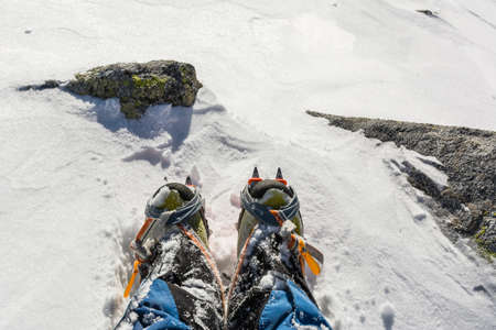 crampons: Boots with crampons on snow
