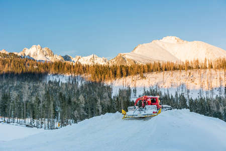 snowcat: Snowcat while working with the surrounding mountains in the background Stock Photo