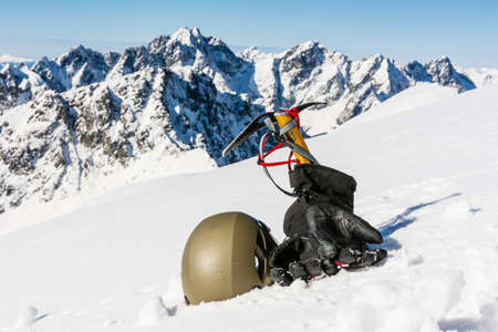 ice axe: Helmet, gloves and ice axe with mountain ridge in the background Stock Photo