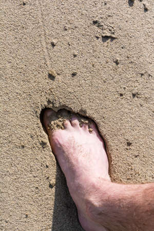 Foot in the sand on the beach