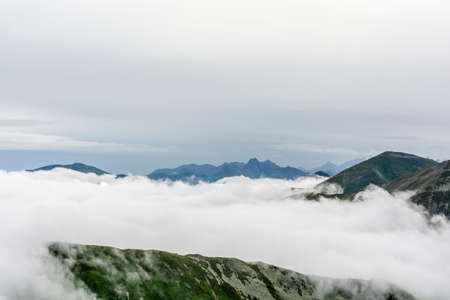 protrude: Tangle of clouds in the valley, only peaks protrude and creating islands Stock Photo