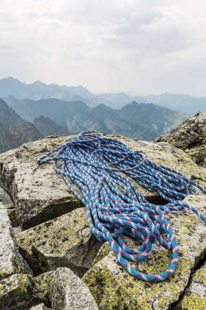 belaying: Rope is located on boulders after finishing climb to the top of the mountain