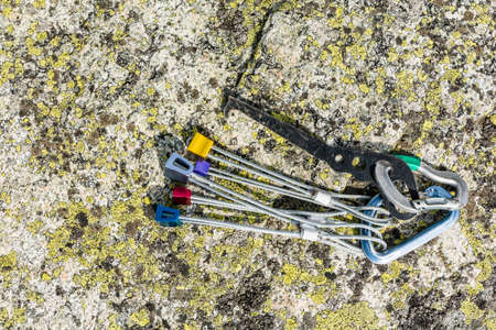 karabiner: Set of nuts and a nut removal tool on a rock with lichen