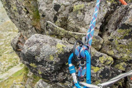descender: Blue dynamic rope in rappel device in mountains