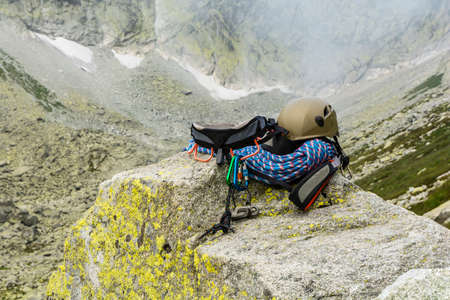 descender: Dynamic rope, helmet, carabiners, climbing harness and descender on the rock in valley