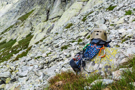 descender: Dynamic rope, helmet, carabiners, climbing harness and descender on a rock in the valley