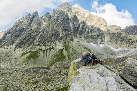 karabiner: Dynamic rope, helmet, carabiners, climbing harness and descender on a rock with a prominent peak in the background
