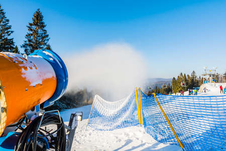 off piste: Snow cannon during the production of artificial snow off piste.