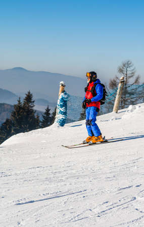 downhill skiing: Wierchomla Mala, Poland - January 02, 2016: Mountain rescuer in the Beskidy Mountains in Poland (GOPR - Mountain Volunteer Search and Rescue) go downhill skiing.
