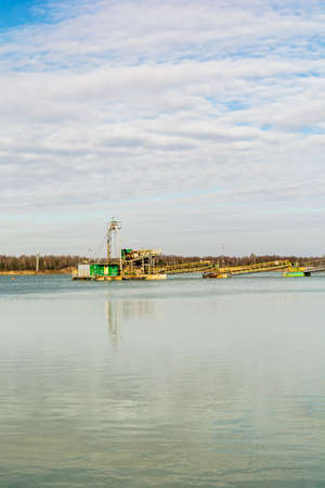 mining ships: Digger dredging in the gravel pit water. Stock Photo