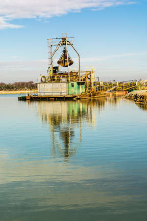 gravel pit: Dredging moored in the gravel pit water. Stock Photo