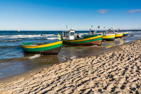 spring tide: Group of fishing boats moored at the beach.