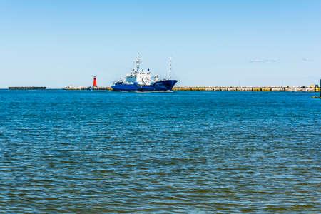 affecting: Gdansk, Poland - June 7, 2016: Ship affecting port flows past the lighthouse.