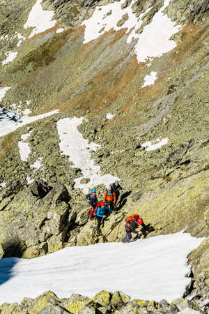 gully: High Tatras, Slovakia - June 18, 2016: Mountain guide takes steps in the snow for a group of clients which leads couloir in the mountains.