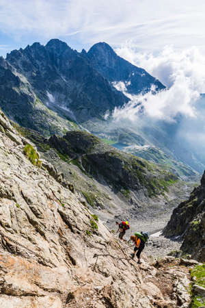 insured: High Tatras, Slovakia - June 23, 2016: Couple of tourists out of the pass in the mountains trail insured chains.