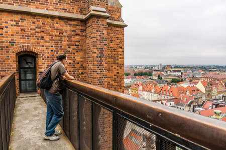 Wroclaw, Poland - August  05, 2016: Man admiring the city from the bridge between the towers.