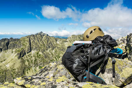 gully: Guide book, helmet and backpack, which attributes the tourist and mountaineer. Stock Photo