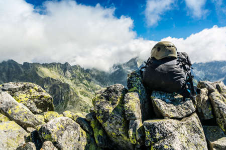 gully: Black backpack with helmet on the summit and clouds over the ridge. Stock Photo