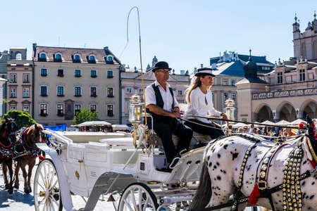 tourists stop: Krakow, Poland - August  26, 2016: A couple fiacres carriage on the white droshky.