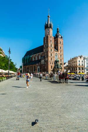 assumed: Krakow, Poland - August  26, 2016: Droshkies and St. Marys Church in Krakow. Editorial
