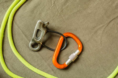 karabiner: Belay device, D-shaped carabiner and dynamic rope or climbing hardware.  Stock Photo